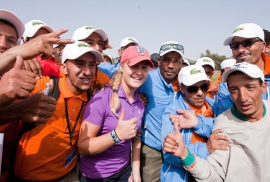 Charley Hull of England gives the thumbs up as she is surrounded by Moroccan caddies on the 18th green in celebration of her first LET victory