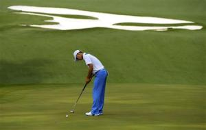 Fourteen-year-old Amateur Guan Tianlang of China sinks a birdie putt on the 10th green during first round play in the 2013 Masters golf tournament in Augusta